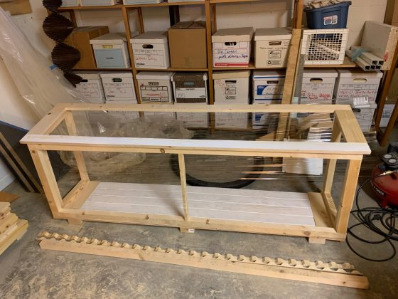 A wooden catio frame on a concrete floor..